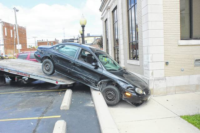 A 1998 Ford Taurus that crashed into the side of the Carnegie Public Library Wednesday morning had to be towed from the scene. At 11:14 a.m., the driver of the Taurus was attempting to park beside another vehicle in the Carnegie parking lot, but was reportedly distracted by a child inside of her vehicle. The driver told police that she accidentally pressed the accelerator pedal, causing her to strike the nearby vehicle and then the retaining wall around the side of the building. The Taurus was stuck on the wall with the vehicle front end resting on the sidewalk. Damage was done to both vehicles. No injuries were reported.