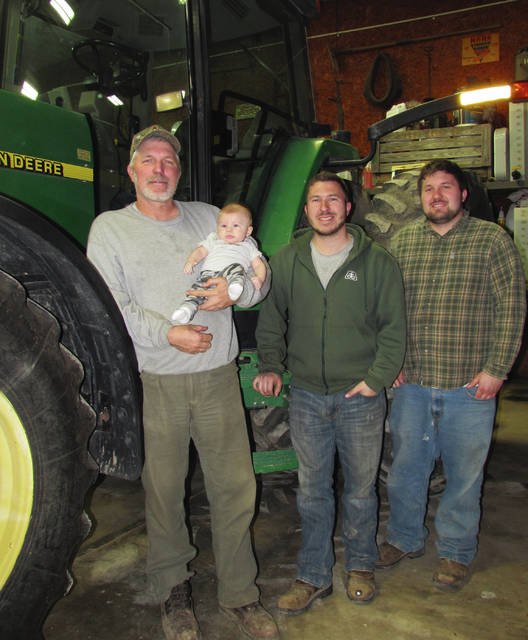 The Montgomery family farmers: Keith, holding grandson Wyle, sons Kyle and Wes (Wyle's dad).