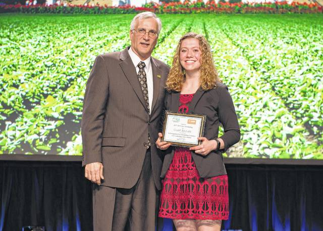 ASA President Ron Moore presents Clare Sollars with the 2017 Soy Scholarship during the annual awards banquet.