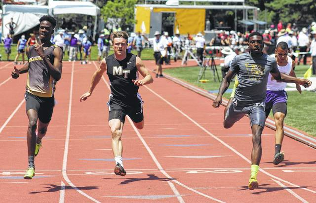 Miami Trace's Drake Litteral (second from left) crosses the finish line in a heat of the 100-meter dash at the 110th annual boys State track meet Friday, June 2, 2017 in Columbus. Litteral advanced to the finals with a new personal best time of 10.98. At left is Wayne Lawrence Jr. of Dayton Meadowdale and at right is Jarquez Cornell of Warrensville Heights. At far right is Tre Ivey of Unioto.