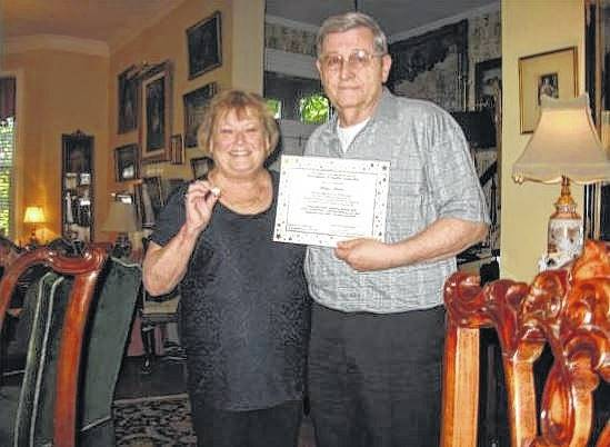 The Genealogical Society President presenting Danny Gilmore with a First Families pin and certificate.