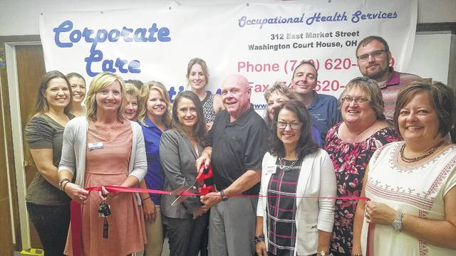 Corporate Care Solutions Medical Director, Kenneth Writesel gets the ribbon cutting honors while surrounded by staff and Chamber ambassadors.