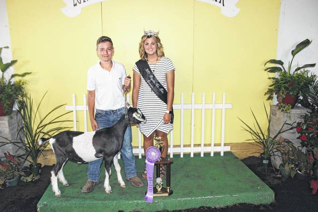 Hunter Roush won the dairy goat reserve champion trophy at Tuesday's Fayette County Junior Fair Dairy Goat Show. Roush is pictured with Fair Queen Marissa Sheets.