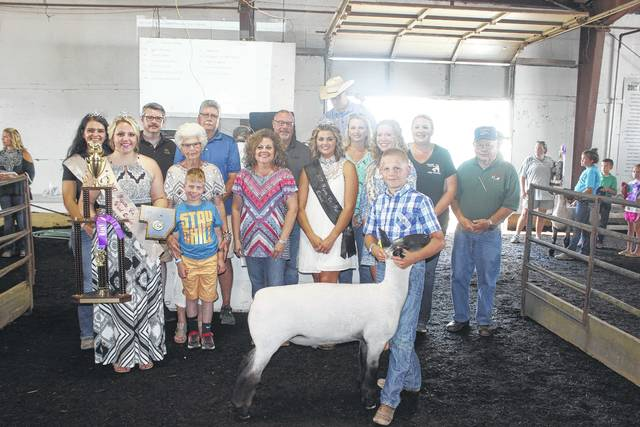 Thaddeus Stuckey's grand champion market lamb sold for $1,500 at the Fayette County Fair Market Sheep Show on Friday evening. Stuckey is pictured with buyers and fair royalty: (front row) Sheep Queen Macy Detty, (second row) Fair Attendant Susanna Eckstein, Loretta Stuckey and Wylee of Stuckey Farms, Diane Faris Munro of Faris Insurance, Fair Queen Marissa Sheets, Fair Attendant Clare Sollars, (back row) Keith Tooill of McDonald's, Mark Richards of First State Bank, Buck Minyo of LCNB, Tabby Melvin of Universal Dermatology, Michelle Bennett of Roller Haven, and Jim Chrisman of the Fayette County Republicans.