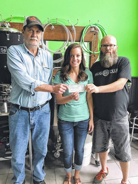 Carolyn Moore (center), Hospice of Fayette County marketing and fundraising Coordinator, is pictured with Mark Underwood and Cliff Rhoads, owners and Brew Masters of Pour Boys' Brew House during a recent donation to Hospice.
