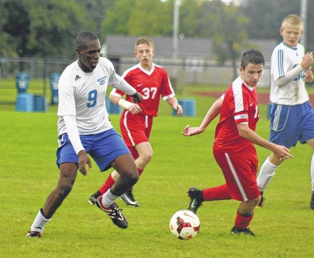 Washington junior Blaise Tayese (9) manuvers the ball away from a defender from Jackson High School during a Frontier Athletic Conference match at Washington High School Tuesday, Sept. 12, 2017. Also pictured for the Blue Lions (at right) is senior Jack Luebbe.