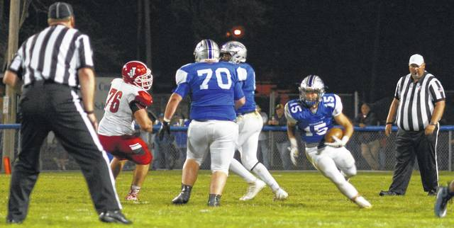 Jacob Rice (15) carries the ball for the Blue Lions in the game versus the Jackson Ironmen Friday night. He is flanked by Jacob VanMeter (70) and Marcell Garrett defending him as Chucky Morris (76) for Jackson attempts to move in.