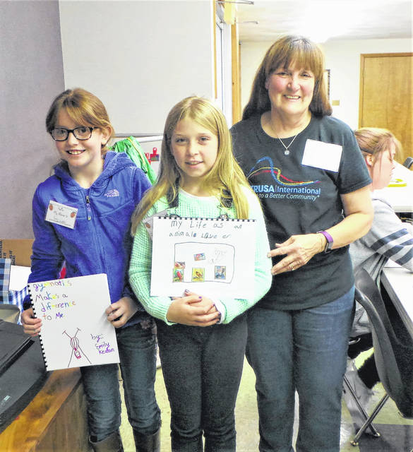 "Two young girls show off their newly-created books, based around the theme of ""X Makes a Difference to Me."" Emily (on left) has described her love of gymnastics, and Bailey (in center) has written about being an animal lover. Altrusan Debra Grover (on right), who has just bound the books, headed the Washington C.H. Altrusa Club's service project along with co-chairs Elaine Crutcher and Anne Quinn. Other members of the club supplied refreshments, stuffed treat bags and acted as ""editors"" during the Saturday afternoon workshop."