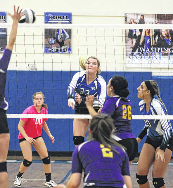 Washington's Delaney Greer (33) makes the hit during a Frontier Athletic Conference match against McClain Tuesday, Oct. 3, 2017 at Washington High School. Also pictured for Washington are Tabby Woods (00) and Hannah Haithcock (at right).