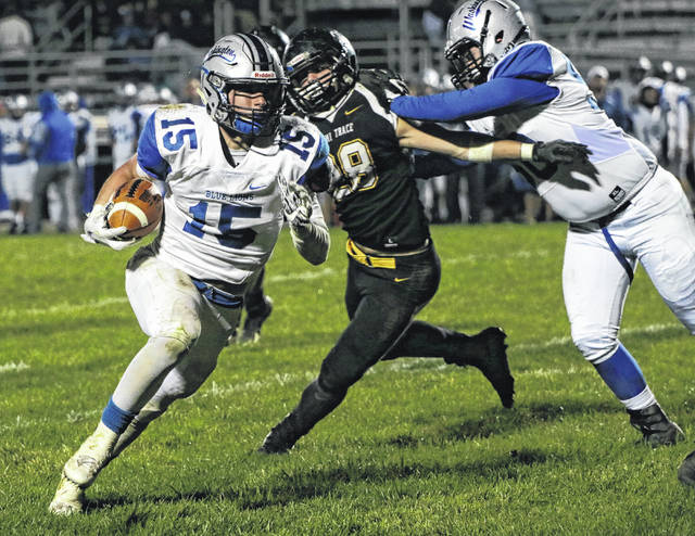 Washington's Jacob Rice (15) carries during the Fayette County rivalry game against Miami Trace Friday, Oct. 27, 2017. Pictured for Miami Trace is Josh Liff (28) and also for the Blue Lions is Drew Moats (50).