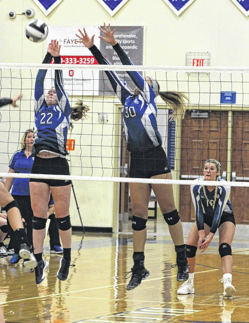 Halli Wall (22) and Hannah Haithcock (30) go up for the block attempt during a Division II Sectional match against Fairfield Union Wednesday, Oct. 18, 2017 at Washington High School. Also pictured, at right, is Faith Kobel and at left, head coach Ashley DeAtley.