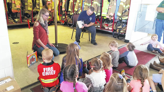 Captain Tim Downing reads to the story time children about fire safety.