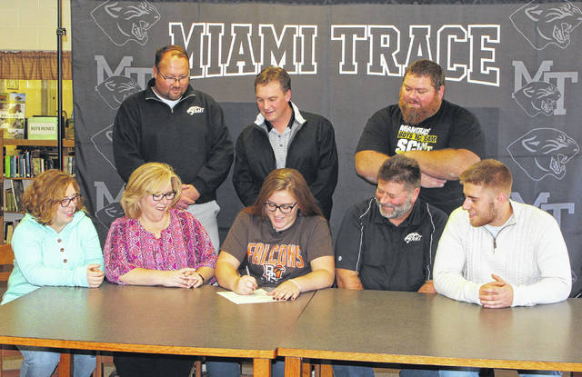 Katie Seyfang, seated, middle, signs a letter of intent on Thursday, Nov. 9, 2017 to attend Bowling Green State University in 2018. She is joined by (front, l-r); her sister, Rae Seyfang, her parents, Ricky and Mike Seyfang and her brother, Wes Seyfang and (standing, l-r); Miami Trace High School track and field coach Brent Noes, coach Chip Wilt and coach Jeff Bennett.