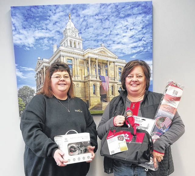 Mindy Cook (left), the Elf on the Shelf Christmas Giveaway winner, and Fayette County Chamber of Commerce President Whitney Gentry pose with a few prizes won by Cook in the holiday promotion.
