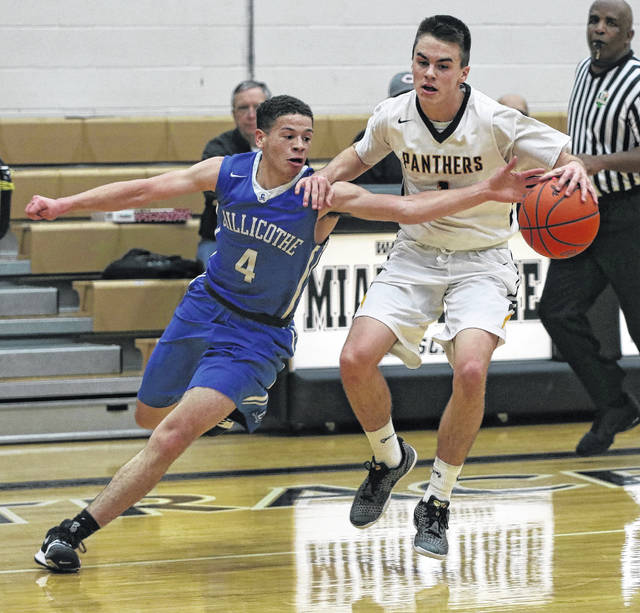 A pair of seniors battle as Miami Trace's Cameron Carter (1) keeps the ball at arm's length against Jalen Jordan of Chillicothe during a Frontier Athletic Conference game at Miami Trace High School Friday, Dec. 8, 2017.