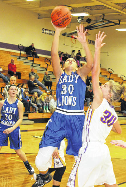 Washington junior Hannah Haithcock (30) puts up a shot for two of her game-high 23 points at McClain High School during a Frontier Athletic Conference game Saturday, Dec. 16, 2017. Pictured for McClain is junior Bryn Karnes (30) and also pictured for Washington is junior Tabby Woods (20). Haithock had 10 rebounds in the game for a double-double performance.