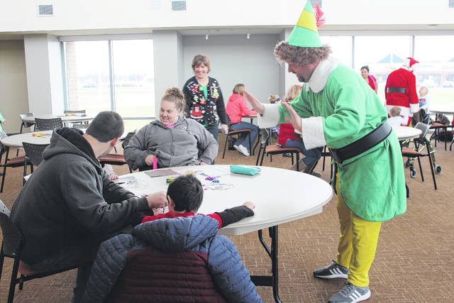 Fayette Progressive Schools were able to treat students to a Polar Express Christmas event on Tuesday morning and afternoon thanks to a donation from the Altrusa Club of Washington Court House. Pictured is Buddy the Elf visiting with a family during the event at Southern State Community College.