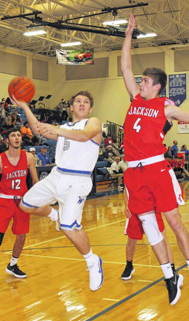 Washington Blue Lion sophomore Miguel O'Flaherty (5) puts up the shot while guarded by Jackson senior Payton Speakman (4) during a Frontier Athletic Conference game Friday, Dec. 15, 2017 at Washington High School. Also pictured for Jackson is junior Cooper Donaldson (12).