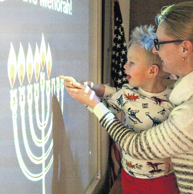 Miss Noel helps Hunter light the Menorah during Hanukkah Storytime at the Carnegie Public Library