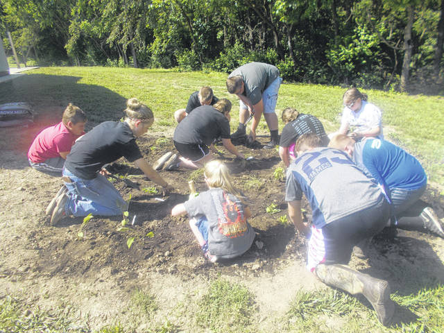 Fayette Farm Life 4-H Club members planting native flowers at the Fayette Fish and Game Building.