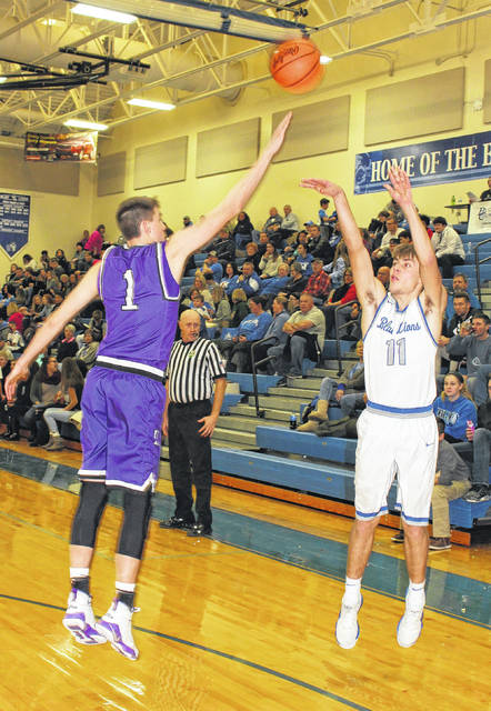 Washington Blue Lion sophomore Garitt Leisure puts up a shot over the fingertips of Logan's Bo Myers during a non-conference game at Washington High School Tuesday, Jan. 2, 2018.