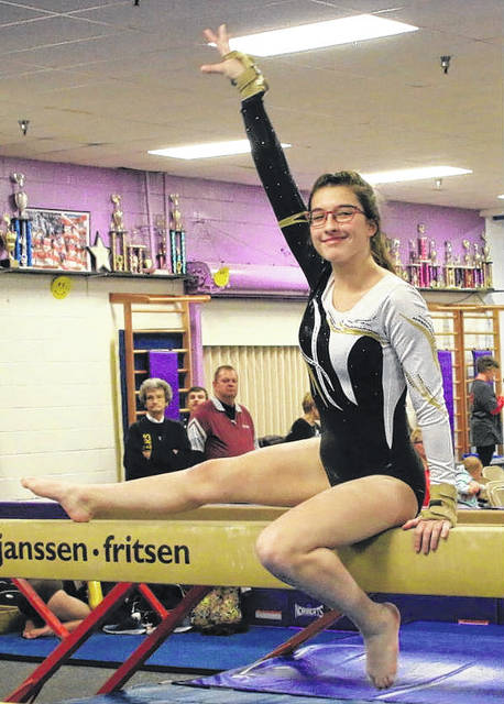 Grace Rolfe poses on balance beam.