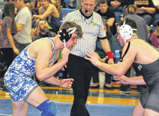 Washington sophomore Collier Brown (left) squares off against Miami Trace senior B.J. Anders in a 182-pound match at the Sectional tournament Saturday, Feb. 24, 2018 at Washington High School.