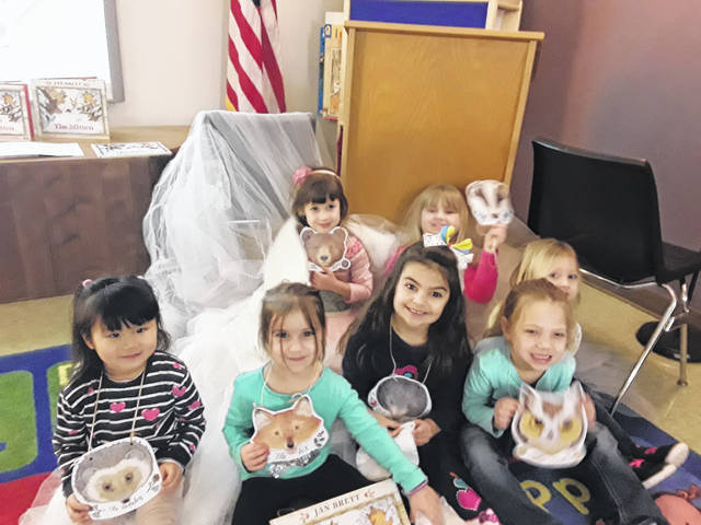 "At storytime this week, children acted out the play ""The Mitten"" based on the classic book by Jan Brett. The actors each played an animal who wanted to stuff itself into a mitten to get out from the cold. Pictured (L-R) are Haniko, Felicity, Hartlyn, Macy, Adrianna, Ellie, and Abby."