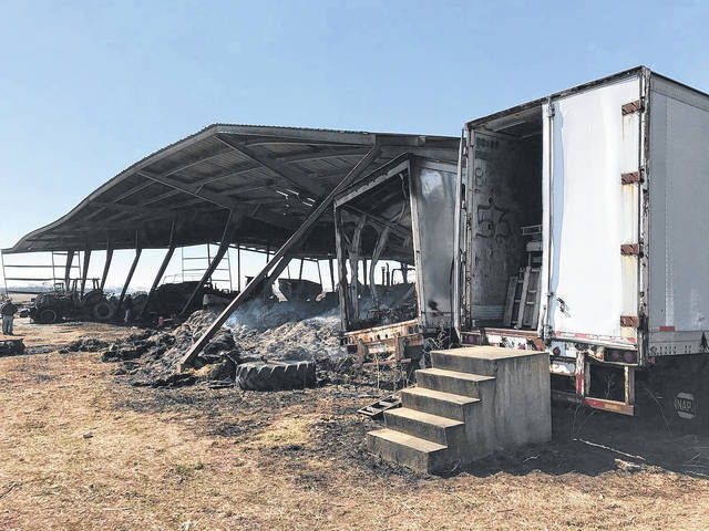 The state fire marshal's office spent time at the fire scene Monday as the investigation continues into the cause of the fire that destroyed a barn and farm machinery.