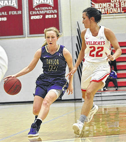 Taylor University senior Josie Cobb, left, brings the ball up-court against Indiana Wesleyan Feb. 23, 2018.