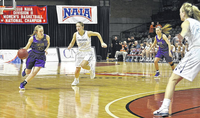 Taylor University senior Josie Cobb (at left) brings the ball up the floor during an NAIA Division II round of 16 game against Concordia Friday, March 9, 2018 in Sioux City, Iowa.