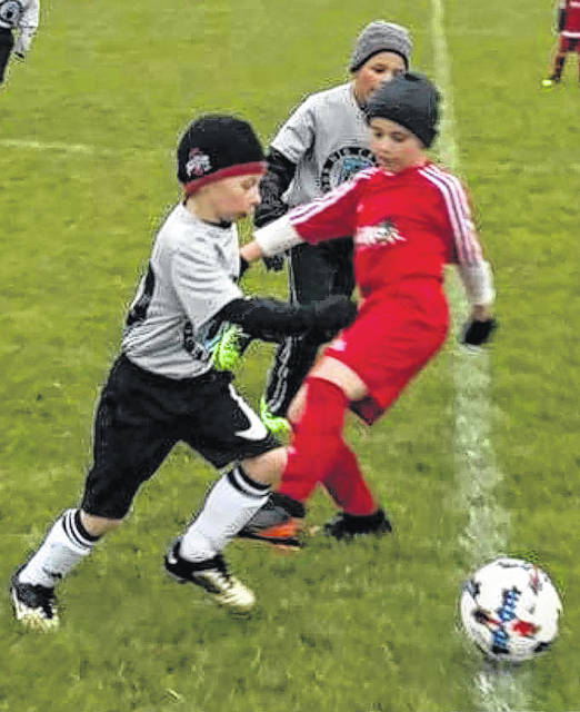 Cam Thoroman, left, eludes a defender from the Warrior FC, a team based out of Huber Heights, as he takes the ball up the field. Also pictured from the Big Cats Soccer Club is Matticks Hernandez.