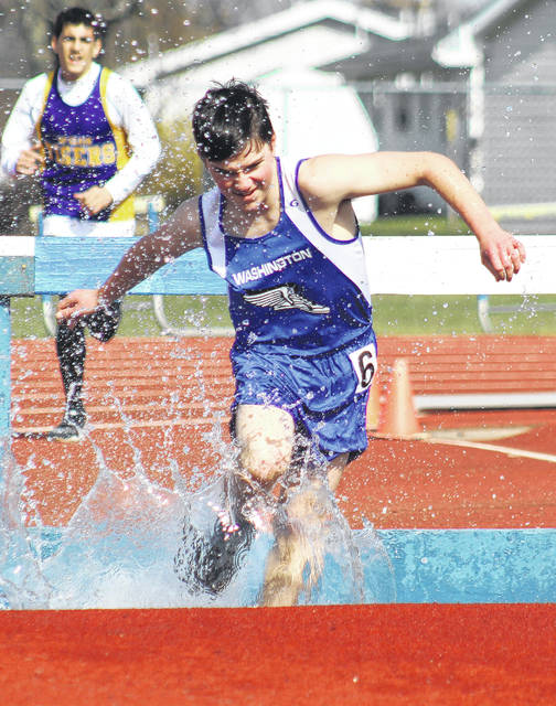 Washington's Conner Lane makes a big splash during the running of the 2000-meter steeplechase at the Blue Lion Invitational at Washington High School Friday, April 13, 2018.