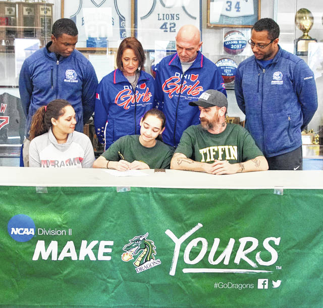 Washington High School senior Courtney Walker, seated, middle, signs a letter of intent to attend Tiffin University where she will continue her education and her wrestling career. She is joined by her parents, Tyra Knisley (left) and Scott Walker (right) and in back, Washington assistant wrestling coach Marlin Ellis, Team Ohio girls coaches Tracie Shore and George Shore and Washington head wrestling coach Louis Reid.