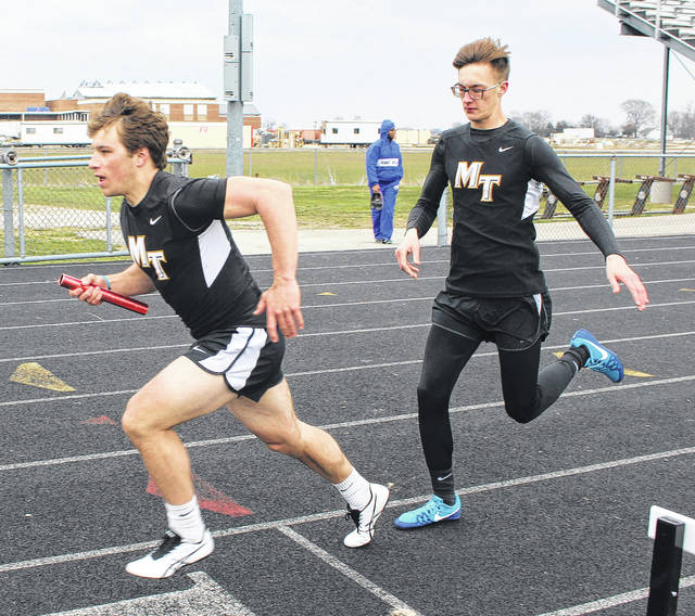 Cole Enochs (left) begins his leg of the 4 x 200-meter relay after having taken the baton from Devin Howard Tuesday, April 10, 2018 at Miami Trace High School.