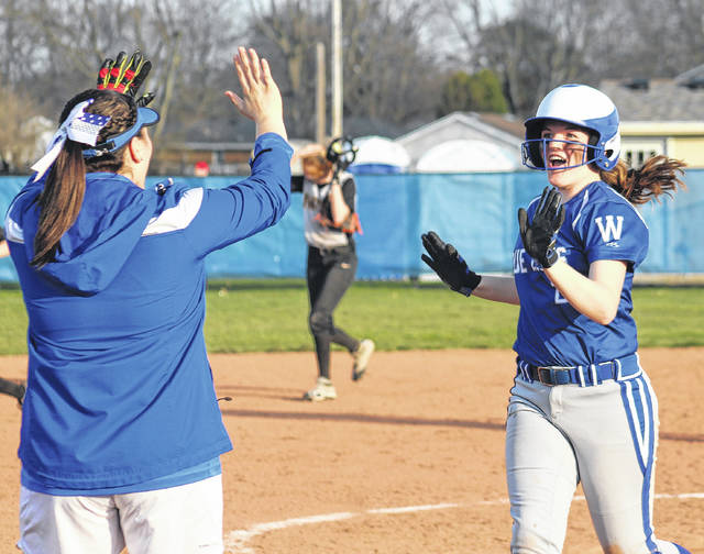 Maddy Jenkins, right, prepares to greet assistant coach Wendy Hawk after Jenkins had the game-winning hit in the bottom of the seventh for Washington in a Frontier Athletic Conference game against Miami Trace Friday, April 13, 2018 at Washington High School.