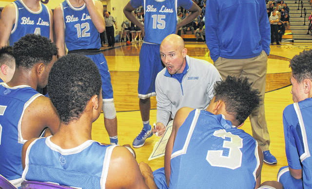 Shannon Bartruff discusses the play he wants his team to run during a timeout in a game from the 2016-17 basketball season. Bartruff announced his resignation as head boys basketball coach for the Washington Blue Lions on April 2, 2018.