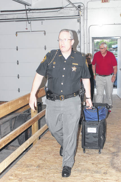 Fayette County Sheriff's Office Chief Deputy Andy Bivens helps collect ballots during the 2018 May primary Tuesday evening. Several Fayette Republican Central Committee races were contested, and several poll workers said the race for Fayette County Auditor continued to keep the day steady with voters.