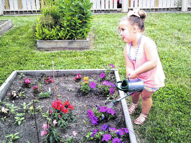 """Reagan waters the children's garden at Carnegie Public Library during the library's program, """"Story Time!"""""""