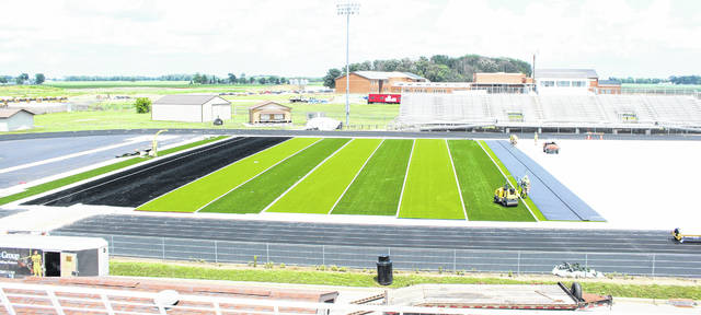 "Work progresses on the new football field at Miami Trace High School. Above, workers lay another section of turf Wednesday afternoon, June 20, 2018. At left is the north end zone. ""Miami Trace"" will be painted on one end zone with ""Panthers"" on the other. The first soccer game to be played on the new field is a boys contest scheduled for Tuesday, Aug. 21 at 5 p.m. against Circleville. The first varsity football game on the new field will be Friday, Aug. 24 against Circleville. (This does not include any soccer or football scrimmages on the new field.)"