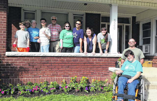 From left to right, neighbor helper, shelter administrator Christy Dunlap, book club facilitator Kathy Ison, book club member Chase Smith, neighbor Jack Thompson, book club member Chris Bell, assistant Leandra Jones, book club member Casey Hackworth, Modern Woodman member and book club facilitator Debra Grover, and book club members Mike and Kelly Annon.