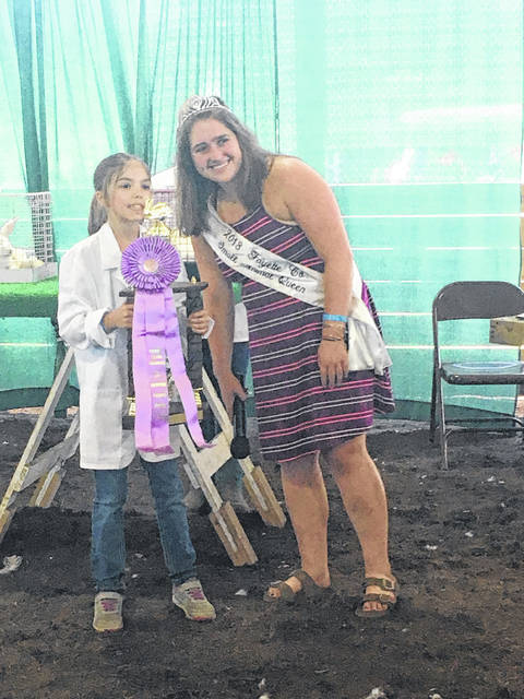 Market Rabbit Show Reserve Grand Champion Alyvia Atkinson receives her trophy from Small Animal Queen Aubrey Schwartz.