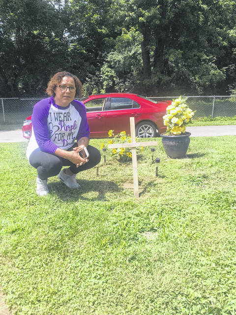 "Nikki Virts poses beside the marker of her father, Kimball Pettiford's grave. The handmade wooden cross says ""Daddy"" with a heart."
