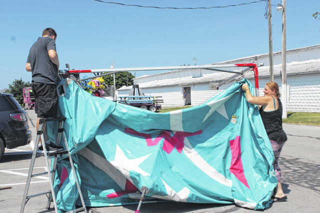 The Fayette County Fair set-up was in full swing Friday. Brenden Lee and Rebecca Worrell place their booth just outside the Mahan Building.