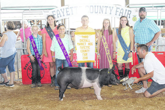 Kylan Knapp (holding banner) won third place overall market hog at Wednesday's Fayette County Junior Fair Market Hog Show.