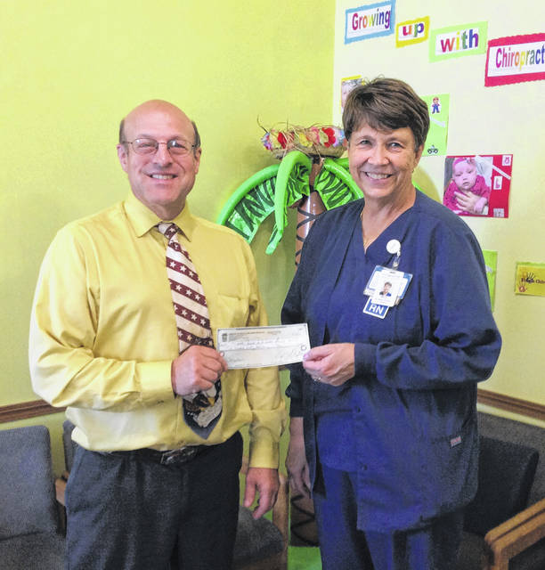Dr. Greg Flerchinger presents a check for $250 to Mary Dye of the Fayette County Diabetes Association.