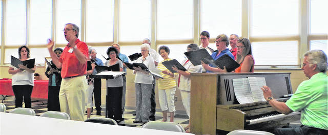 "Retired Miami Trace High School vocal instructor Dick Glass had organized a ""Musical Extravaganza"" as celebratory entertainment following the buffet supper. Fourteen talented members of Glass' Fayette County Choral Society, accompanied on the piano by Washington High School teacher David Penwell, performed patriotic songs in addition to show tunes. Here Glass is shown encouraging the audience to sing along on the final number: the Russian immigrant Irving Berlin's beloved ""God Bless America."""