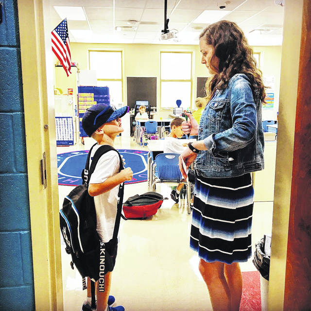 A new second grade teacher to Washington Court House City Schools and Cherry Hill primary, Amber Grigsby, meets with a student on his way in the door on the first day of school.