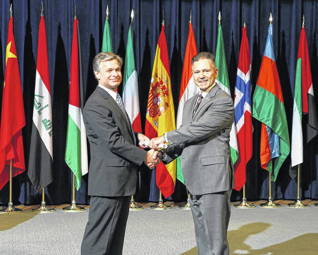 FBI Director Christopher Wray presents Maj. Jon Long (right) with his diploma from the FBI National Academy Program.