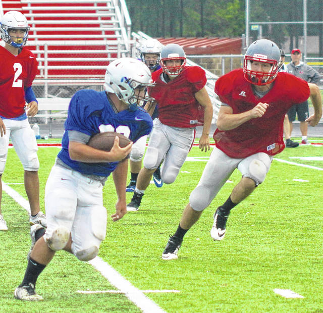 Brandon Cubbage, at left, a sophomore, runs for the Blue Lions during a scrimmage at Goshen High School Saturday, Aug. 11, 2018.